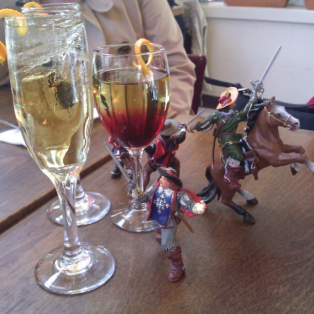 Three musketeer figurines with swords and capes, one riding a toy horse, sitting on a wood grain table next two three champagne cocktail glasses.