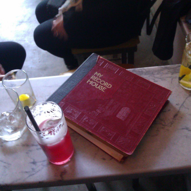 "A cocktail glass with straw and a red mixed drink sitting on a marble counter next to a red album for 45"" records, with words ""My Record House"" printed on the cover in gold letters"